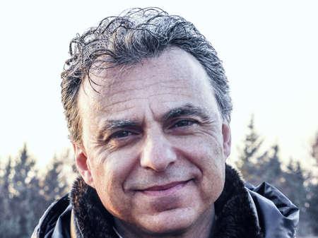 ojos negros: Elegante hombre de mediana edad con los ojos verdes y el pelo sal pimienta vestido con chaqueta acolchada de color azul oscuro está sonriendo tranquilizadoramente en el campo