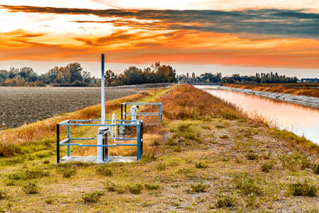divert: Gears and operating means to manage channel to divert river water for irrigation of cultivated fields Stock Photo