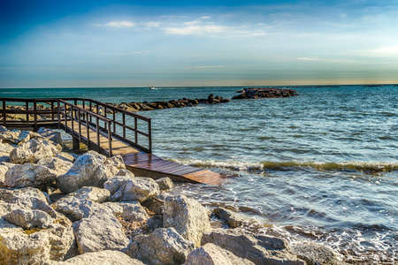 handrails: wooden footbridge with handrails and rocks in the Adriatic Sea
