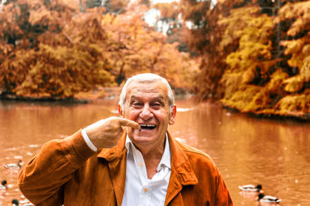 dentures: senior with suede jacket and white shirt in a green park indicates dentures