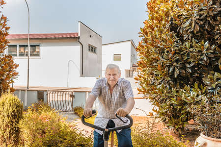 octogenarian: elderly octogenarian male keeps fit by doing exercise bike on the garden of the house Stock Photo