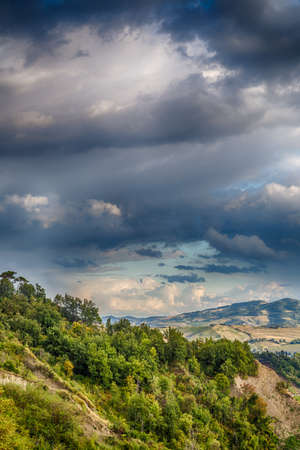ridges: Harmonious serenity of nature and farming on the slopes of the Apennines of Romagna, cultivated fields, orchards and ridges decorated with umbrella pines and cypresses Stock Photo