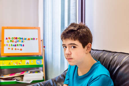 waits: Caucasian teenage boy waits in the waiting room in the dental clinic near a board with some magnetic letters