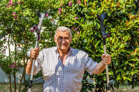 octogenarian: Funny faces of elderly octogenarian male triumphantly holding crutches on the patio of the house Stock Photo