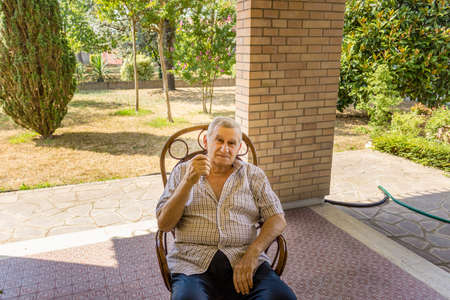 octogenarian: elderly octogenarian male sitting on a chair on the patio of the house