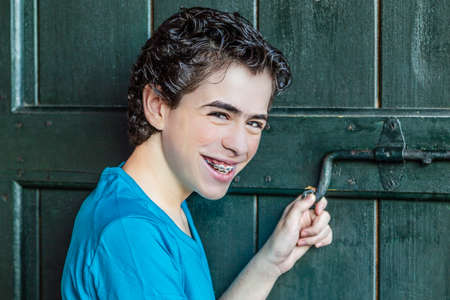 door bolt: smiling teenager shows braces while moving the bolt of an old wooden door