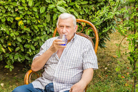octogenarian: elderly octogenarian male drinking a glass of water while sitting on a wicker chair in the garden Stock Photo