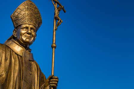 high priest: bronze statue of Saint John Paul II with Crucifix