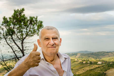thumbs up sign: elderly octogenarian male makes thumbs up sign Stock Photo