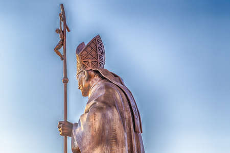 bronze statue of Holy Pope with Crucifix seen from the back