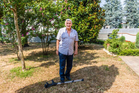 octogenarian: elderly octogenarian male standing on crutches on the patio of the house