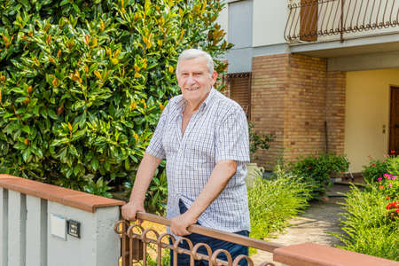 octogenarian: elderly octogenarian male standing on the patio of the house Stock Photo