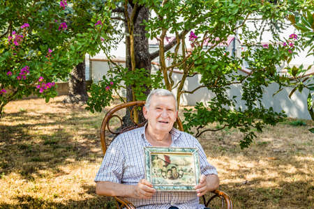 octogenarian: elderly octogenarian male smiling and showing old vintage photo in a frame while sitting on wicker chair in the garden