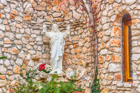 jesus standing: Sacred Heart of Jesus white statue in front of brick stone walls Stock Photo