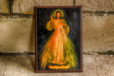 jesus paintings: an icon with the picture of the Merciful Jesus leaning on an old wall: the ribbon on bottom is blank