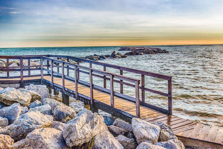 fenced in: fenced wooden walkway on the rocks of the Adriatic Sea in Italy Stock Photo