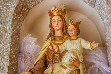 Statue of the Blessed Virgin Mary with Baby Jesus on stone walls