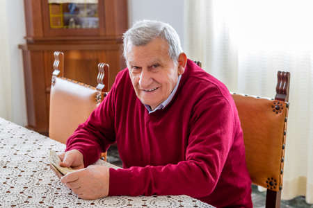 euro banknotes: eighty-year-old man sitting at dining table holding euro banknotes to count them