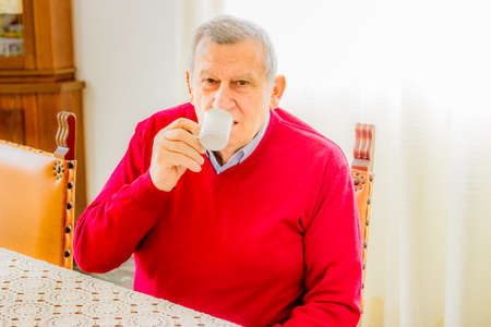 octogenarian: happy old octogenarian sitting at the kitchen table drinks a cup of Italian coffee