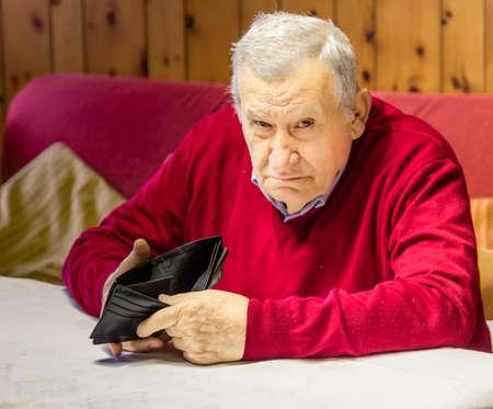 desolate en grimmige oude tachtigjarige zit aan de keukentafel toont een lege portemonnee
