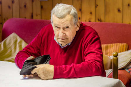 octogenarian: desolate and grim old octogenarian sitting at the kitchen table shows an empty wallet