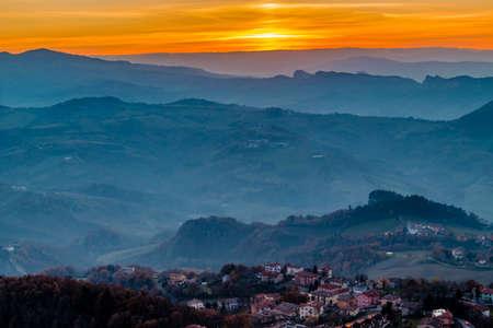 titan: sunset on hilltops in the mist around Titan Mount in the Repubblic of San Marino Stock Photo