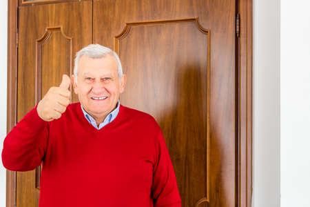octogenarian: octogenarian happy man in red sweater shows thumb up in front of the door Stock Photo