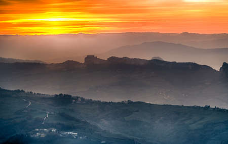 titan: sunset on hilltops in the mist around Titan Mount in the Repubblic of San Marino Stock Photo