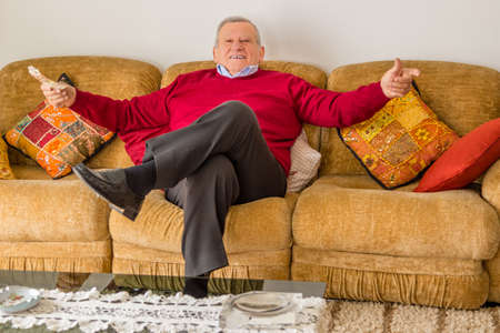 euro banknotes: eighty-year-old man sitting on the couch while opening arms and  holding euro banknotes Stock Photo