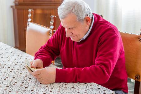 banconote euro: ottanta anni uomo seduto al tavolo da pranzo in possesso di banconote in euro di contarli Archivio Fotografico