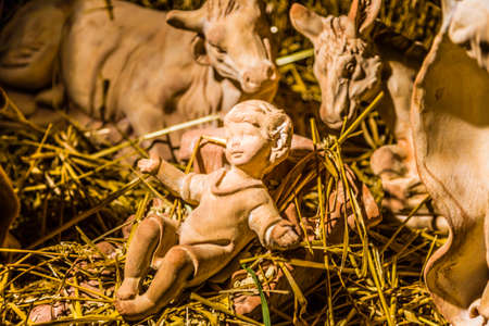 manger: Statues in a Christmas Nativity scene, the Holy Child Jesus in a manger in the straw as the ox and the donkey are warming Stock Photo