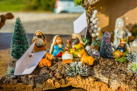 jesus statue: vivid colors of a Christmas Nativity scene, the Blessed Virgin Mary and Saint Joseph watch over the Holy Child Jesus in a manger as the ox and the donkey are warming Stock Photo