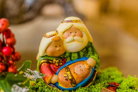 jesus mary joseph: vivid colors of a Christmas Nativity scene, the Blessed Virgin Mary and Saint Joseph watch over the Holy Child Jesus in a manger