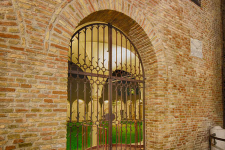locked in: night view of locked gate in front of the portico of a medieval cloister Stock Photo