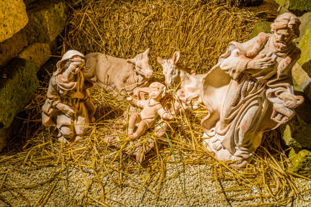 manger: Statues in a Christmas Nativity scene, the Blessed Virgin Mary and Saint Joseph watch over the Holy Child Jesus in a manger in the straw as the ox and the donkey are warming