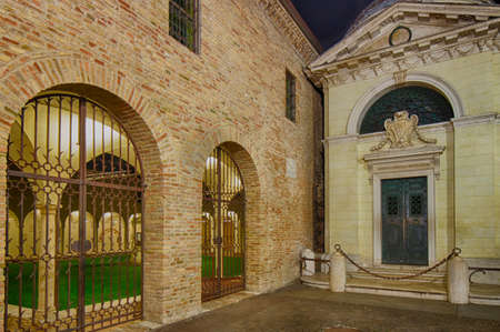 dante alighieri: night view of locked gate in front of the portico of a medieval cloister next to the tomb of Dante Alighieri
