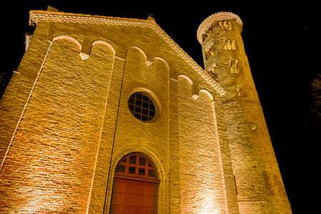 oldest: night view of ancient brick walls of an old Catholic church with one of the oldest  belltowers in Italy