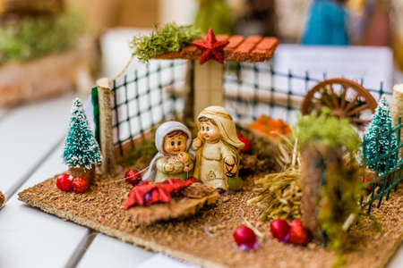 crib jesus: vivid colors of a Christmas Nativity scene, the Blessed Virgin Mary and Saint Joseph watch over the Holy Child Jesus in a manger