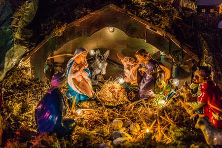 nascita di gesu: Statue in un presepe di Natale, la Beata Vergine Maria e San Giuseppe guardare il Bambino Gesù Santo in una mangiatoia nella paglia come il bue e l'asinello stanno effettuando il riscaldamento Archivio Fotografico