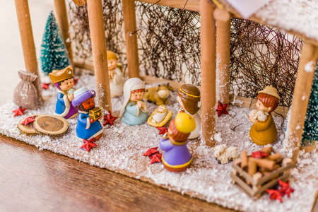 three wise men: vivid colors of a Christmas Nativity scene, the Blessed Virgin Mary and Saint Joseph watch over the Holy Child Jesus in a manger as the ox and the donkey are warming and while three wise men are bearing gifts Stock Photo