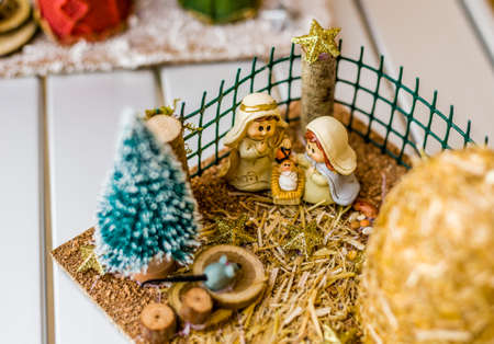manger: vivid colors of a Christmas Nativity scene, the Blessed Virgin Mary and Saint Joseph watch over the Holy Child Jesus in a manger
