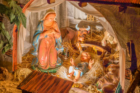jesus mary joseph: Statues in a Christmas Nativity scene, the Blessed Virgin Mary and Saint Joseph watch over the Holy Child Jesus in a manger in the straw as the ox and the donkey are warming