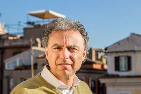 excessive: middle-aged man in green polo with the palaces of Rome in the background squints uncomfortable with excessive light of the sun Stock Photo