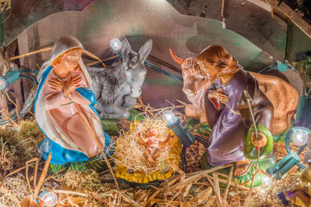 crib jesus: Statues in a Christmas Nativity scene, the Blessed Virgin Mary and Saint Joseph watch over the Holy Child Jesus in a manger in the straw as the ox and the donkey are warming