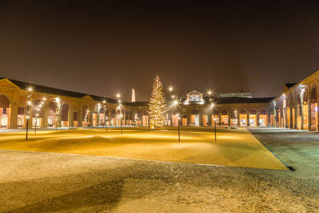 surrounded: Lights and Christmas decorations and Christmas tree in an enclosed square surrounded by loggias and colonnades in Lugo, Italy Stock Photo