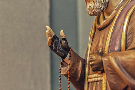 pius: detail of a wood carved statue of Saint Father Pius with his gloved hands to cover the stigmata while holding a rosary
