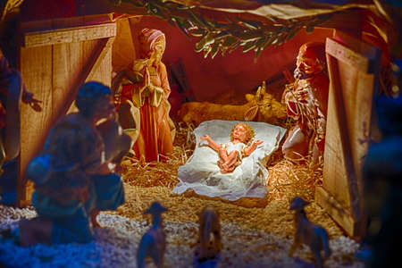 manger: Statues in a Christmas Nativity scene, the Blessed Virgin Mary and Saint Joseph watch over the Holy Child Jesus in a manger in the straw while the ox and the donkey are warming air