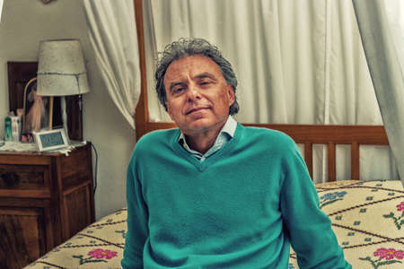 relaxes: middle-aged man relaxes  sitting in the bedroom