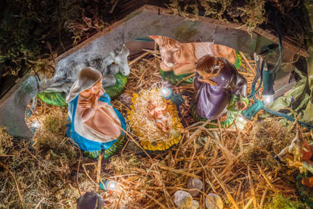 jesus statue: Statues in a Christmas Nativity scene, the Blessed Virgin Mary and Saint Joseph watch over the Holy Child Jesus in a manger in the straw as the ox and the donkey are warming