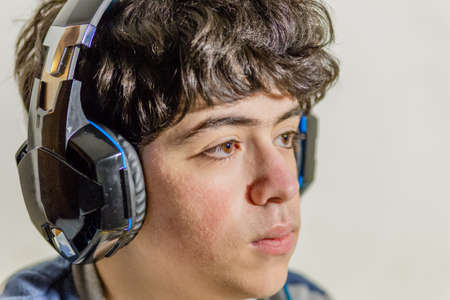 kids playing video games: boy with wearing headphones while playing with video games